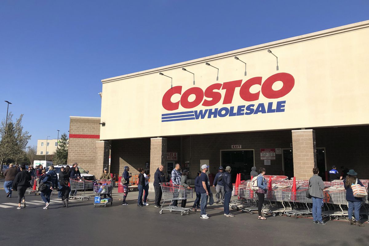 In this March 20, 2020, file photo, shoppers line up to enter a Costco store in Tacoma, Wash. Americans are beginning to see the first economic impact payments hit their bank accounts this week. The IRS tweeted Saturday, April 11, 2020, that it had begun depositing funds into taxpayers' bank accounts and would be working to get them out as fast as it can. (AP Photo/Ted S. Warren, Fle)