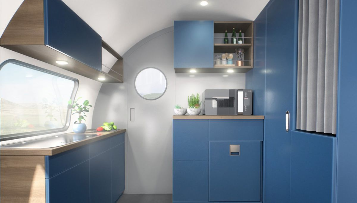 The interior of a camper kitchen with blue cabinets, silver walls, a sink below a large window, and an accordion door on the right.