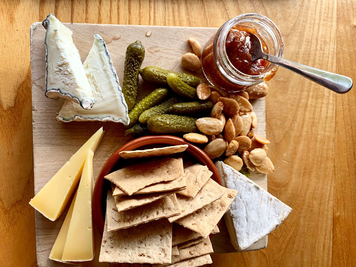 A board with various hunks of cheeses, a pile of crackers, a jar of jam, on a wooden tabletop