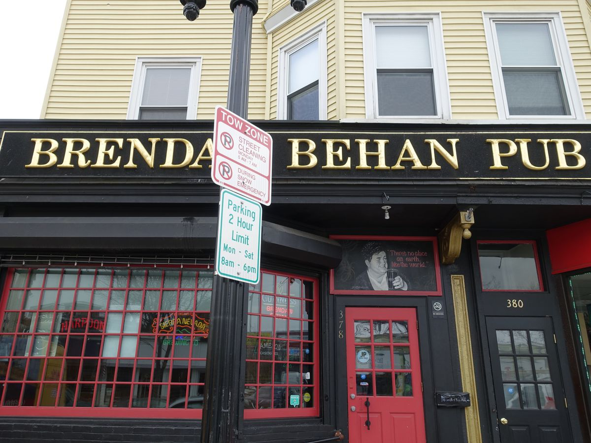 Black exterior of a bar with a red door and red trim around the large front window. Brendan Behan Pub is written in a gold font across the top of the one-story building.