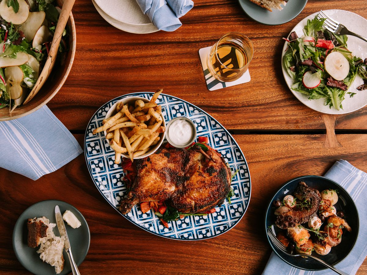 Overhead view of a wooden table covered with plates of New England-y food