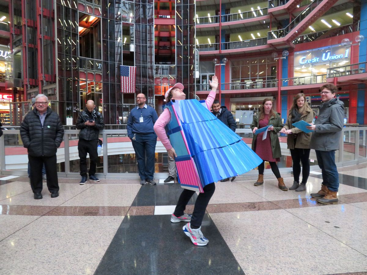 A man poses in an indoor atrium dressed in a blue and pink custom of a wedge-shaped building modeled on Chicago's Thompson Center.