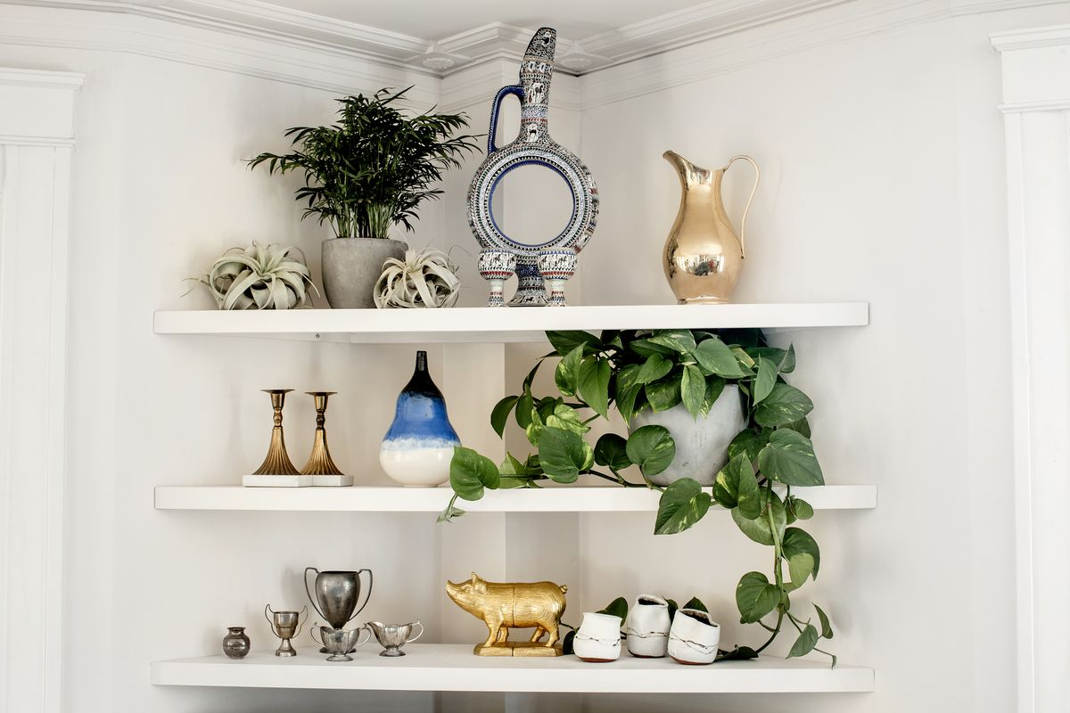 A corner in the living room has three, triangle-shaped shelves. They display keepsakes and curios.