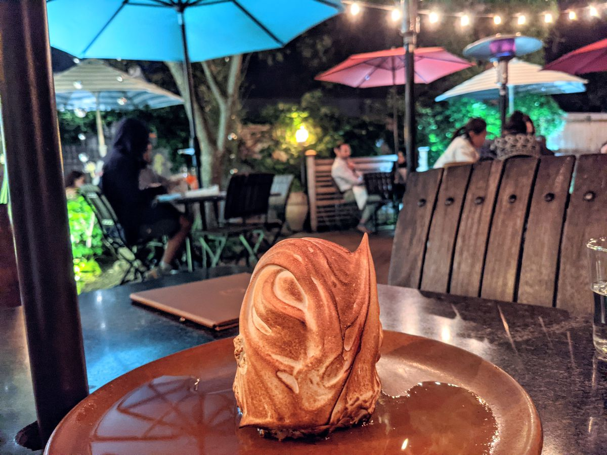 Baked Alaska sits on a plate on a restaurant patio table at night, with brightly colored umbrellas and string lights visible in the background.