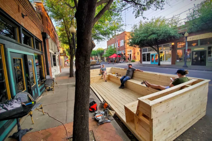 A wooden bench is on the street outside a restaurant. Two people sit on it, far apart.