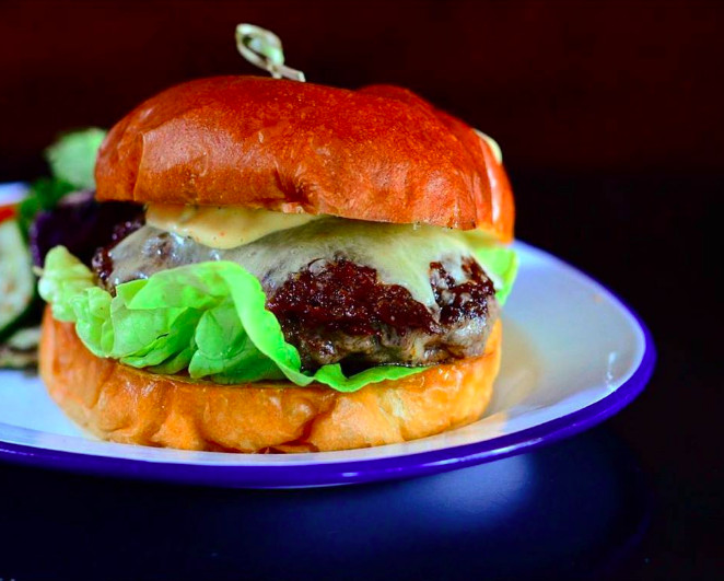 A cheese burger with lettuce and a skewered bun sits on a white plate with a blue rim atop a black surface at Deep Ellum