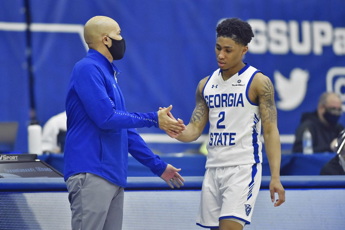Georgia State guard Justin Roberts (2) is greeted by his coach Rob Lanier (left) as he walks off the court during the second half of a college basketball game between the Troy Trojans and Georgia State Panthers on February 19, 2021, at GSU Sports Arena in Atlanta, GA.
