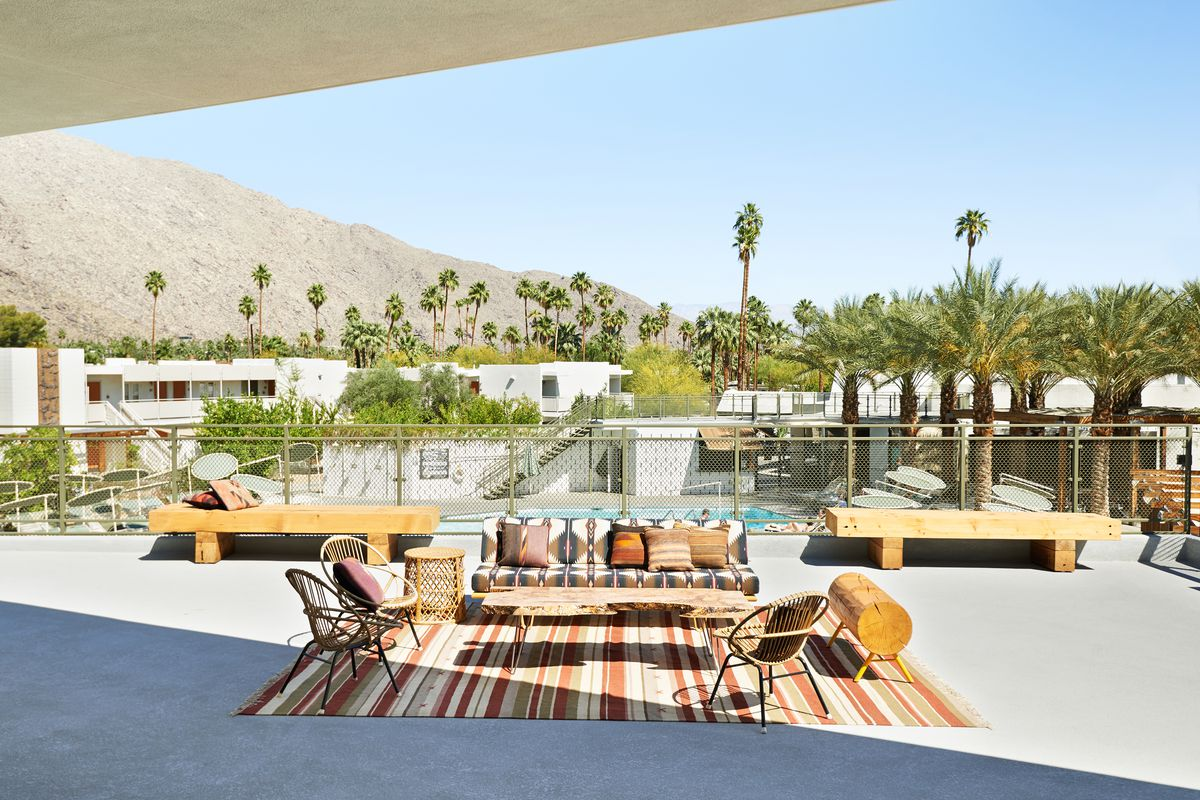 An outdoor seating area with chairs, a couch, a striped area rug, and a swimming pool. There are trees and a mountain in the distance.