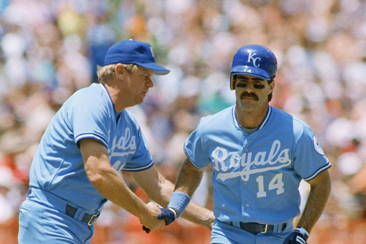 Royals coach Adrian Garrett congratulates Bill Buckner on a home run in 1988. Garrett, a former Cubs player and White Sox minor-league manager, has died at age 78.