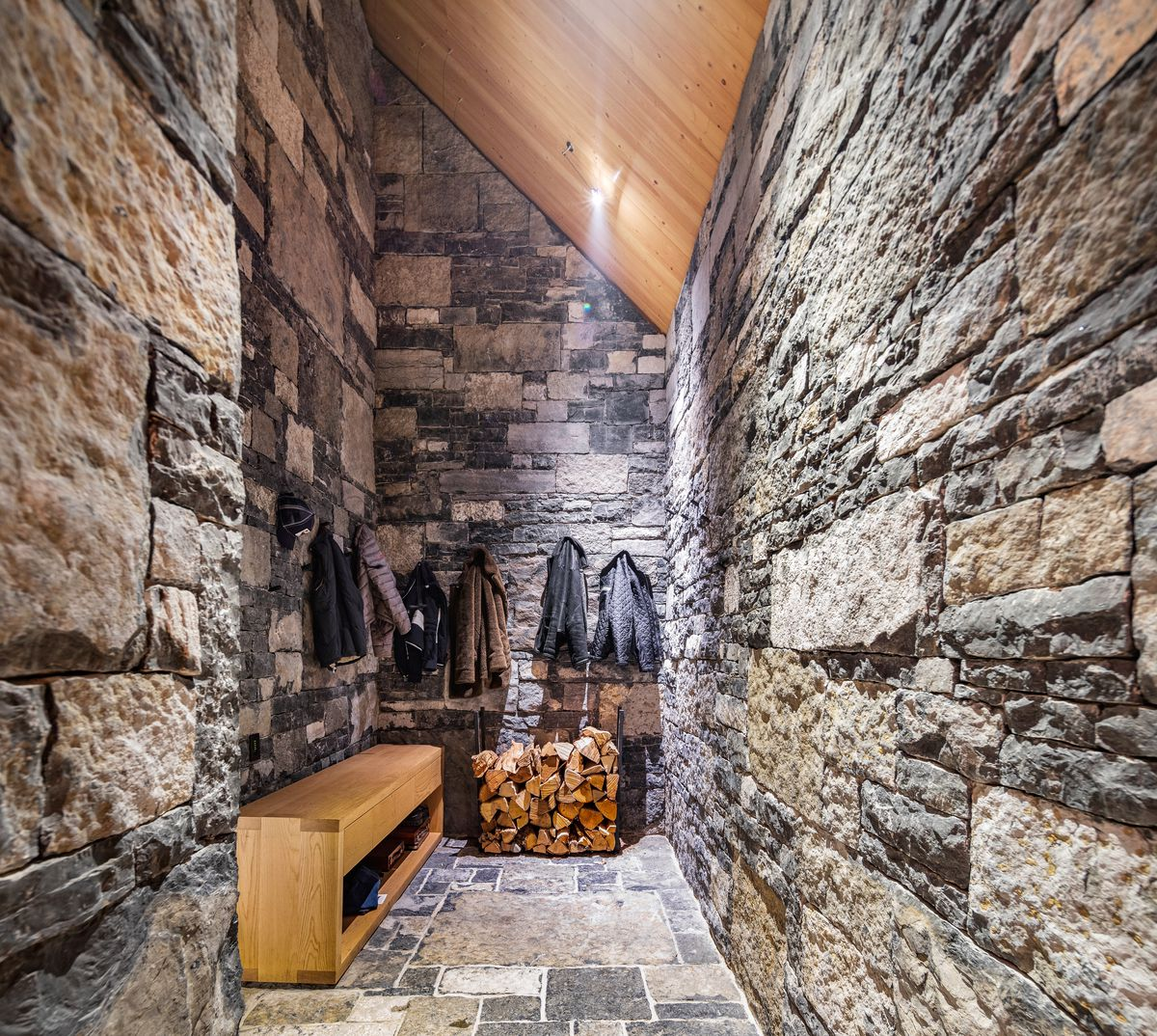 A stone mud room has stone on the walls, a wooden bench, and jackets on the wall.