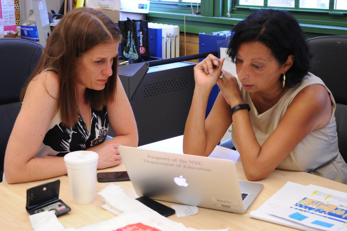 Devon Eisenberg, left, looks over graduation ceremony plans with co-director LeMarie Laureano at the Young Women's Leadership School in the Bronx.