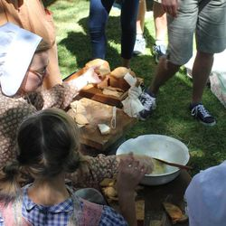 One of the descendants of John Rowe Moyle passes out bread and freshly churned butter to guests at Moyle Park  in July 2014. In addition to churning butter, the park's pioneer activities include making candles, hand washing laundry and dancing.