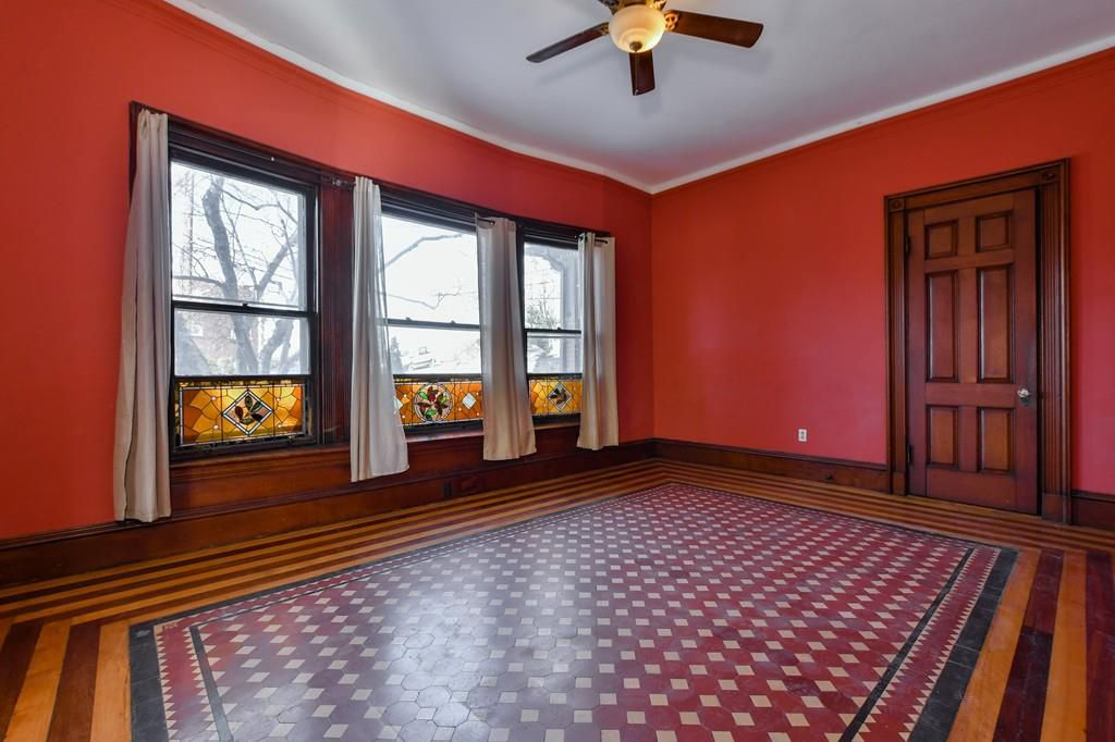 An empty parlor with three windows, a closed door, a ceiling fan, and checkered-patterned floor.