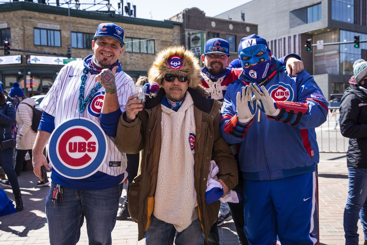 Richie Garcia (center, in white jersey), 47, of Bridgeport, poses for a photo with friends outside Wrigley Field before the Chicago Cubs home-opener against the Pittsburgh Pirates.
