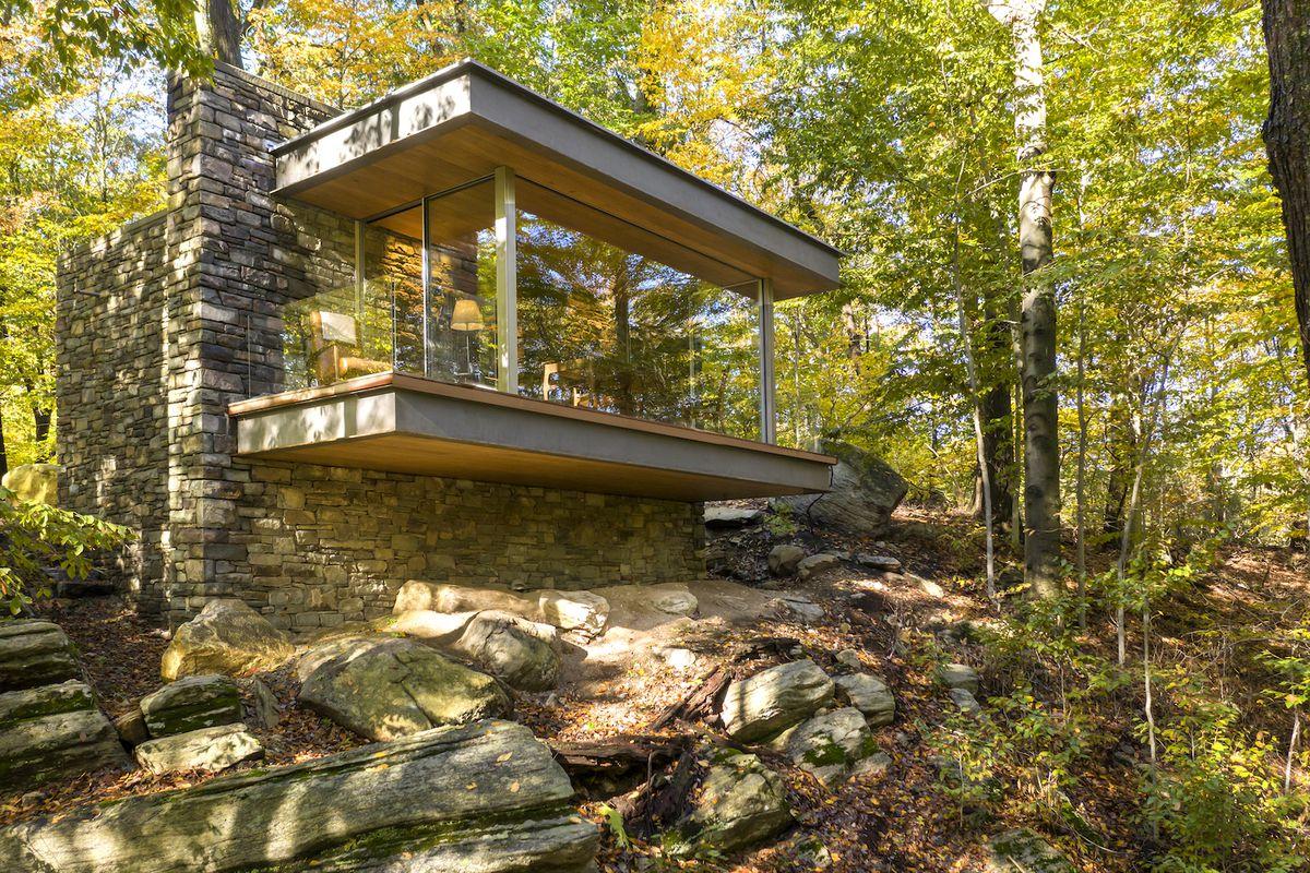 Glass-clad studio in woods.