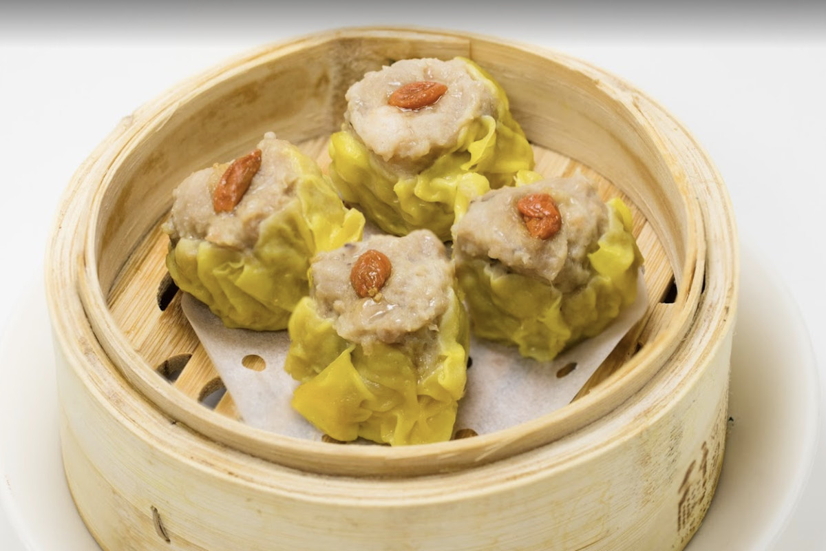 A bamboo steamer with four dumplings.