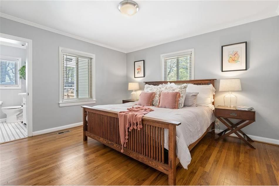 A bedroom with wood floors and a bathroom at left.