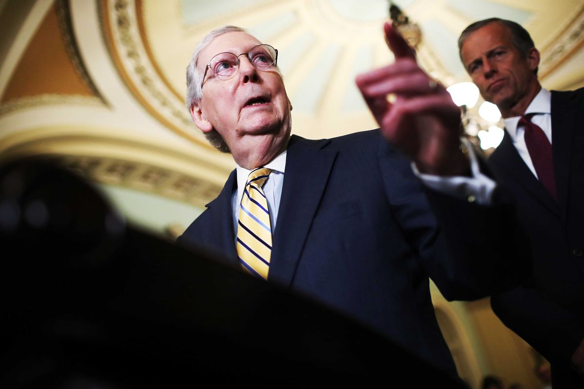 Senate Majority Leader Mitch McConnell gestures during a press conference.