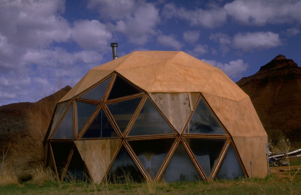 A brown geodesic dome with glass panels. The domed house is in the foreground. There are mountains in the background.