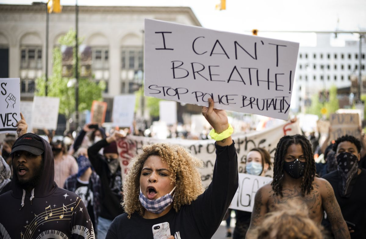 """I can't breathe! Stop police brutality"" a woman's sign reads, her mouth open in a shout."