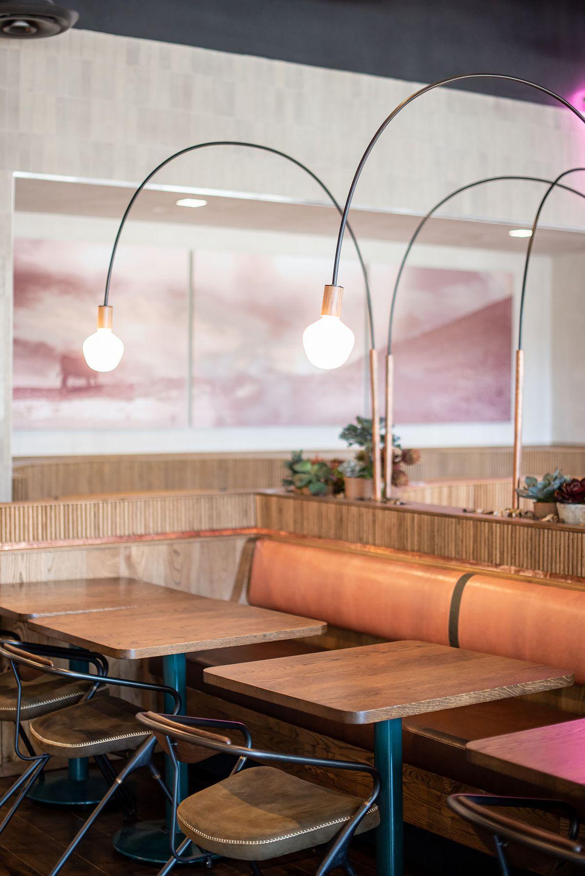 Mid-century lights hover over a low booth.