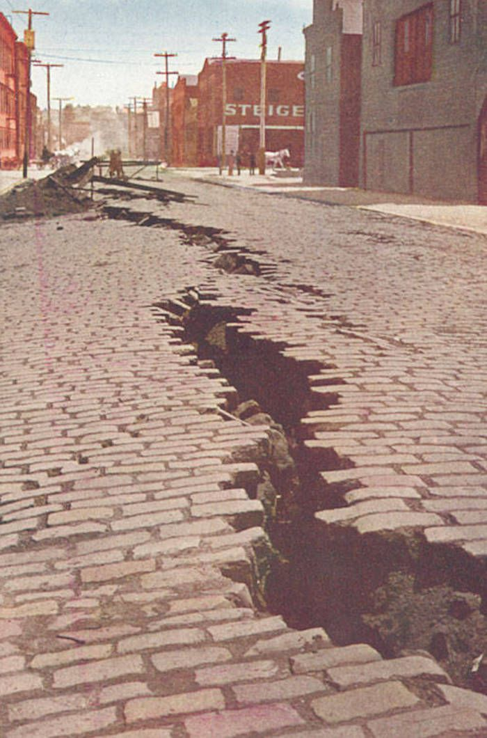 A postcard showing deep fissures in a brick street.