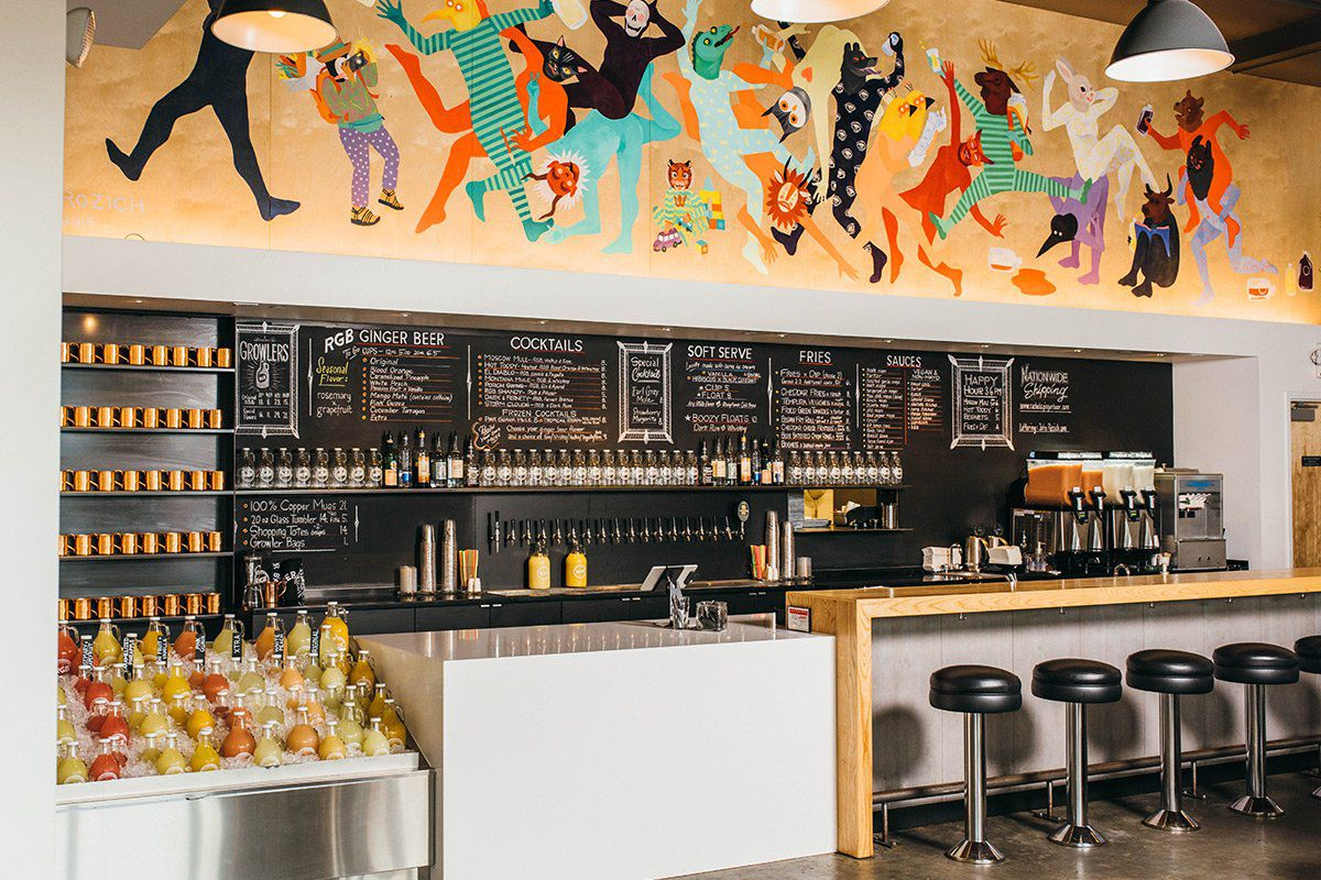 The interior of Rachel's Ginger Beer in Capitol Hill, with a colorful mural above the bar.