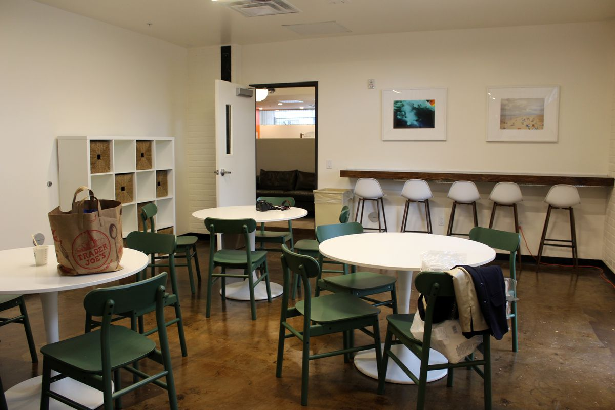 Three white round tables with green chairs in the dining area of the new Gardner Street Women's Bridge Housing Center in West Hollywood.
