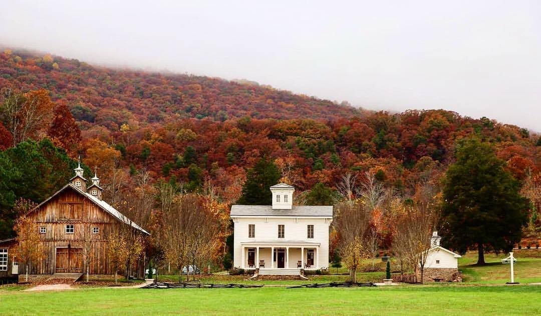 A white farmhouse and barn set against a backdrop of mountains in a full blaze of fall color.