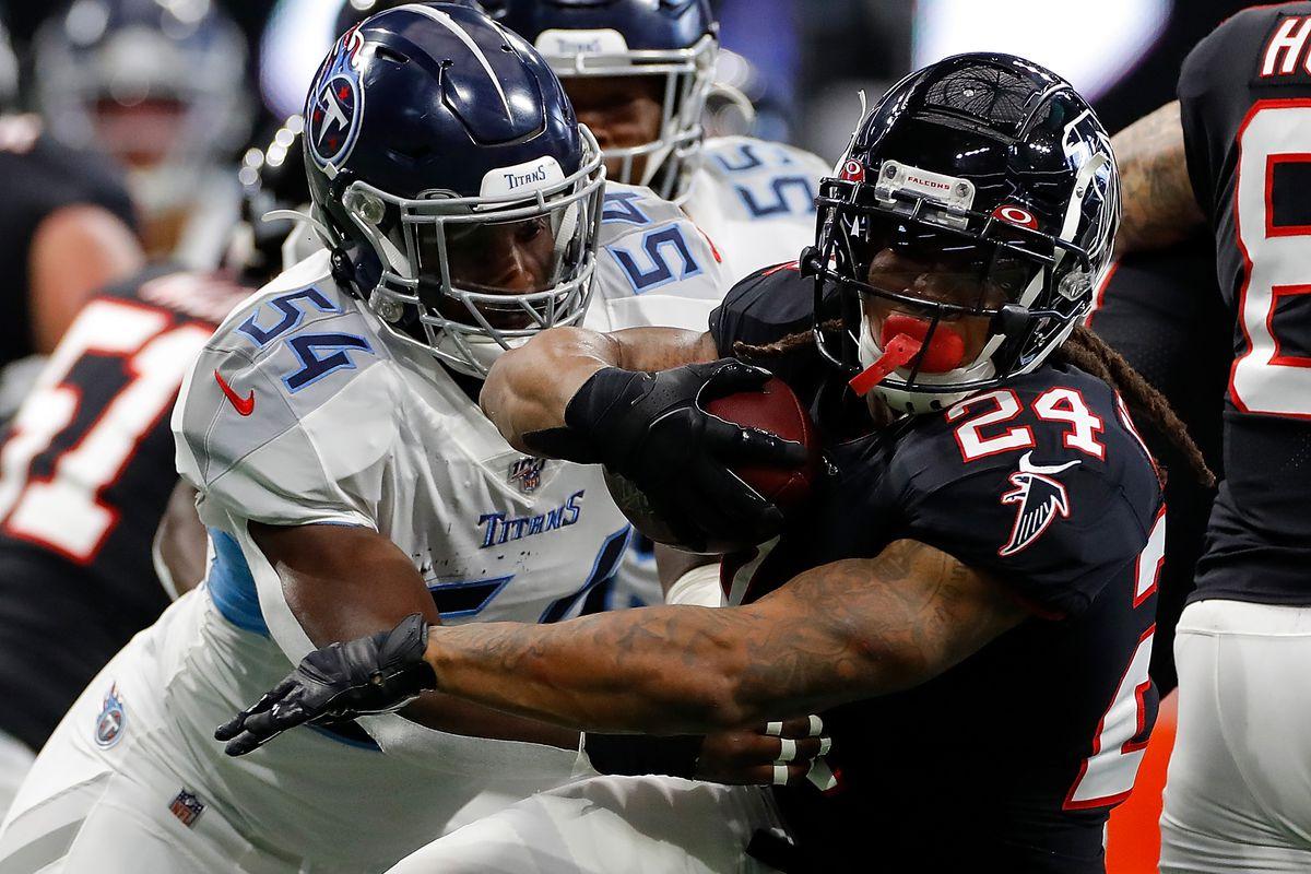 Devonta Freeman of the Atlanta Falcons spins away from Rashaan Evans of the Tennessee Titans at Mercedes-Benz Stadium on September 29, 2019 in Atlanta, Georgia.