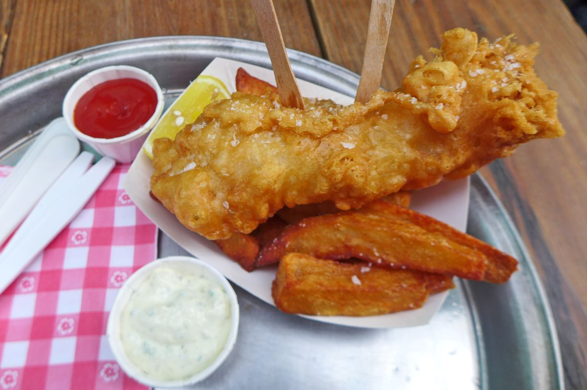 A craggy brown fish filet with rectangular fries log piled underneath on a round metal tray with little cups of ketchup and tartar sauce.