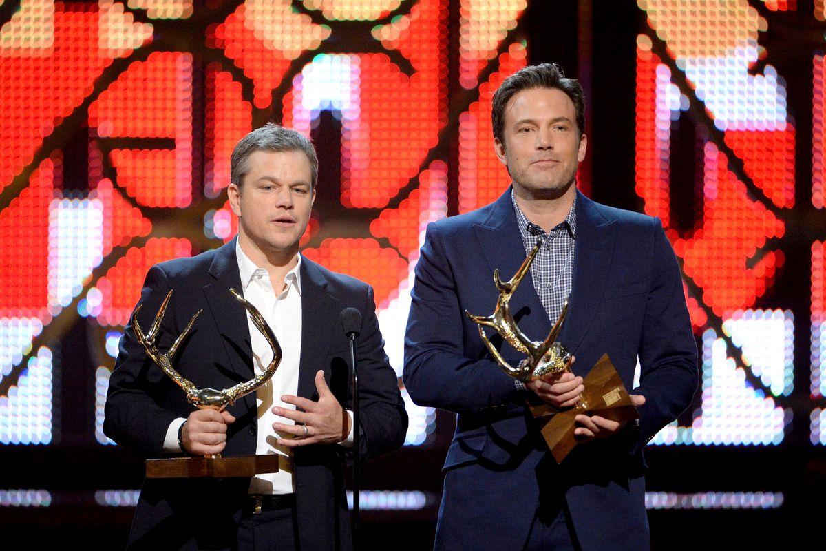 Matt Damon and Ben Affleck holding awards shaped like deer antlers on stage