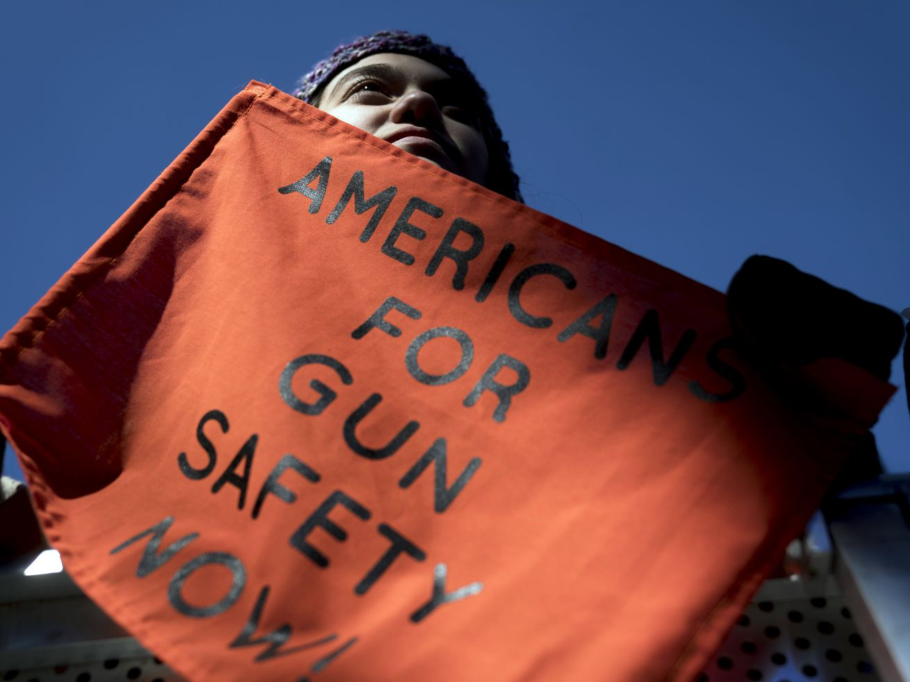 """In this March 24, 2018, file photo, Isabel White of Parkland, Fla., holds a sign that reads """"Americans for Gun Safety Now!"""" during the """"March for Our Lives"""" rally in support of gun control in Washington, that was spearheaded by teens from Marjory Stoneman Douglas High School after the 2018 mass shooting in Parkland, Fla."""