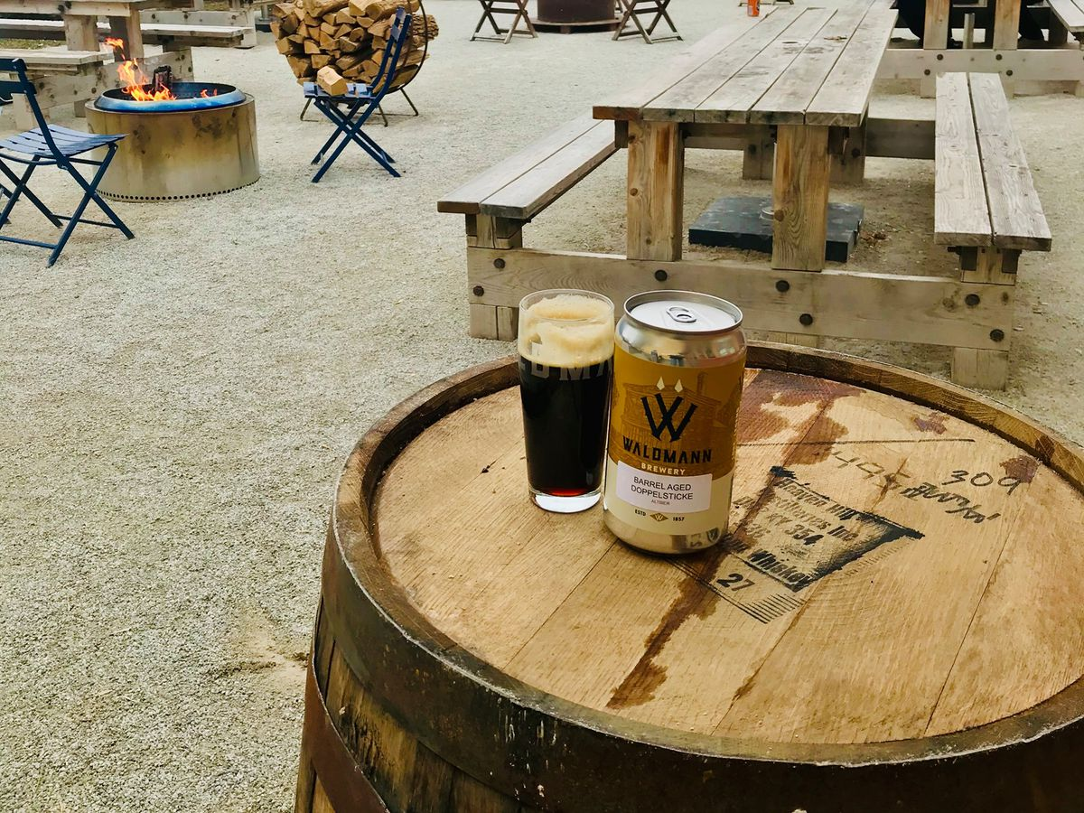 A Crowler and full pint of beer on a barrel outside with the view of a patio with picnic tables and fire pits