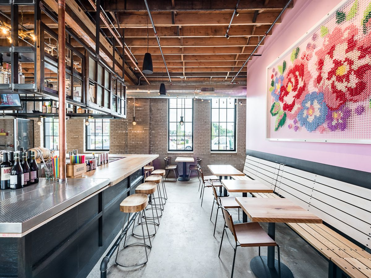The interior including pink walls, with a large cross-stitch looking art installation, a bar, and high booths