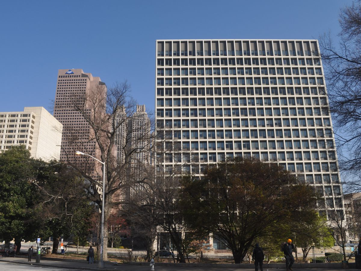 The modern building, seen with the downtown skyline beyond.