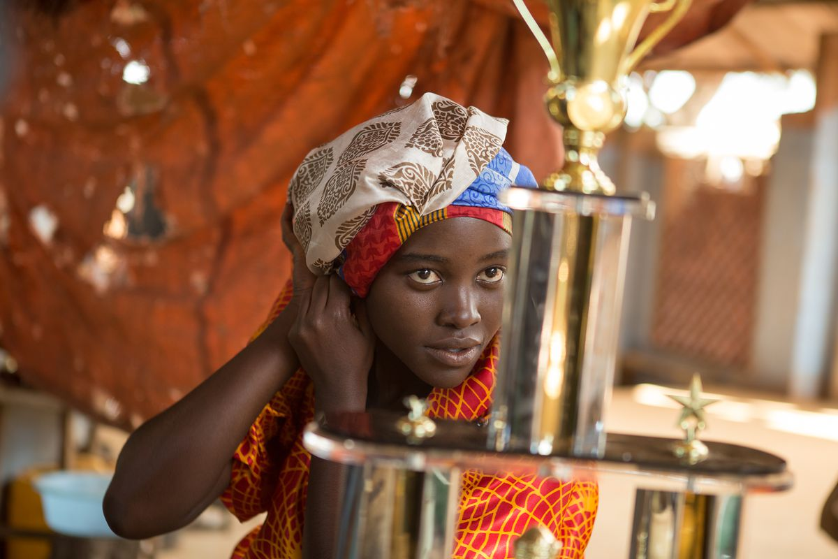 Madina Nalwanga plays Phiona Mutesi, looking at her trophy.