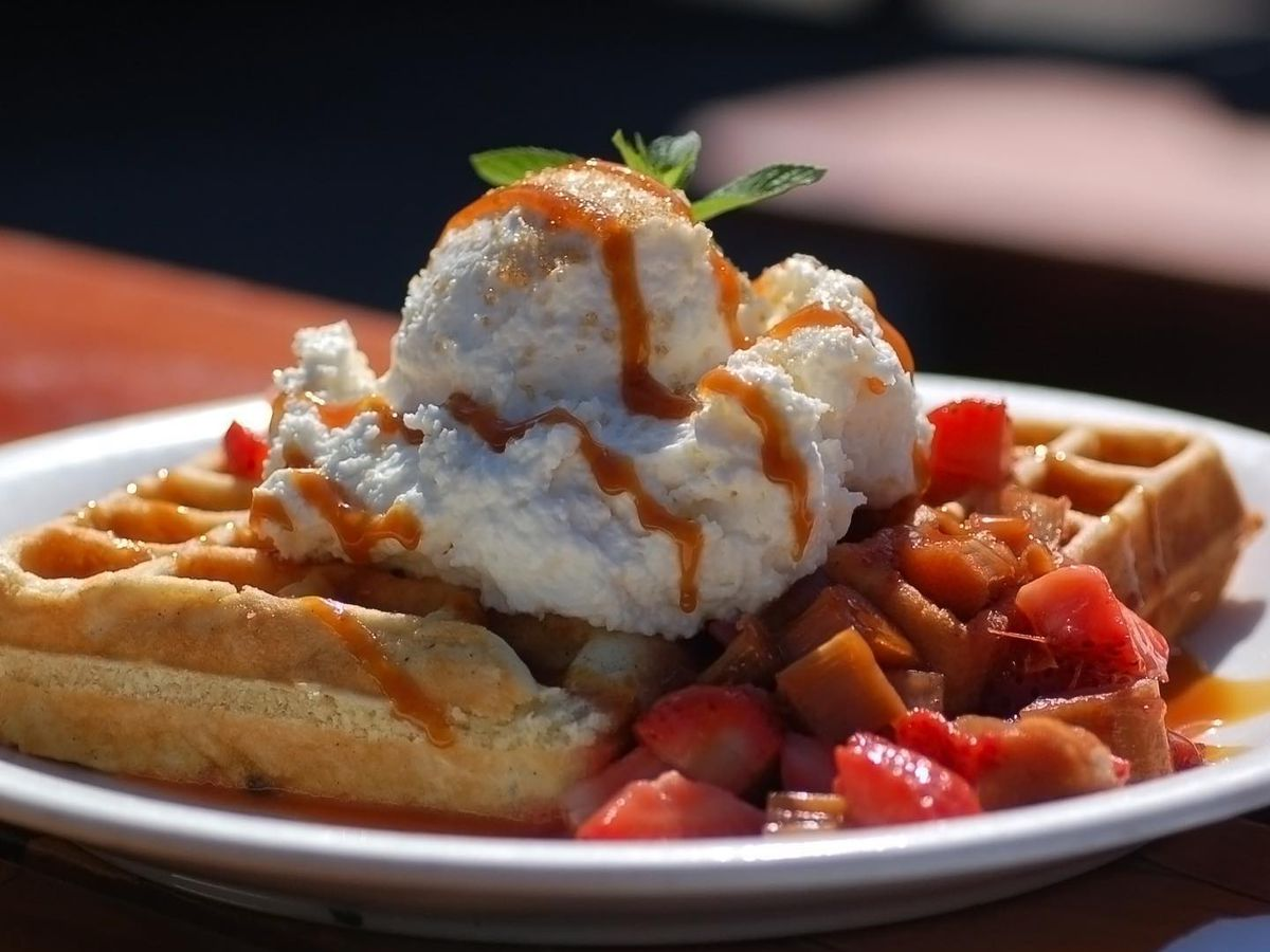 Waffles on a plate topped with whipped cream, fruit, and drizzles of sauce