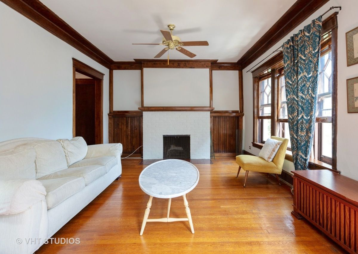 A sofa sits against a wall in a living room with a fireplace and wood window casing and crown molding trim.