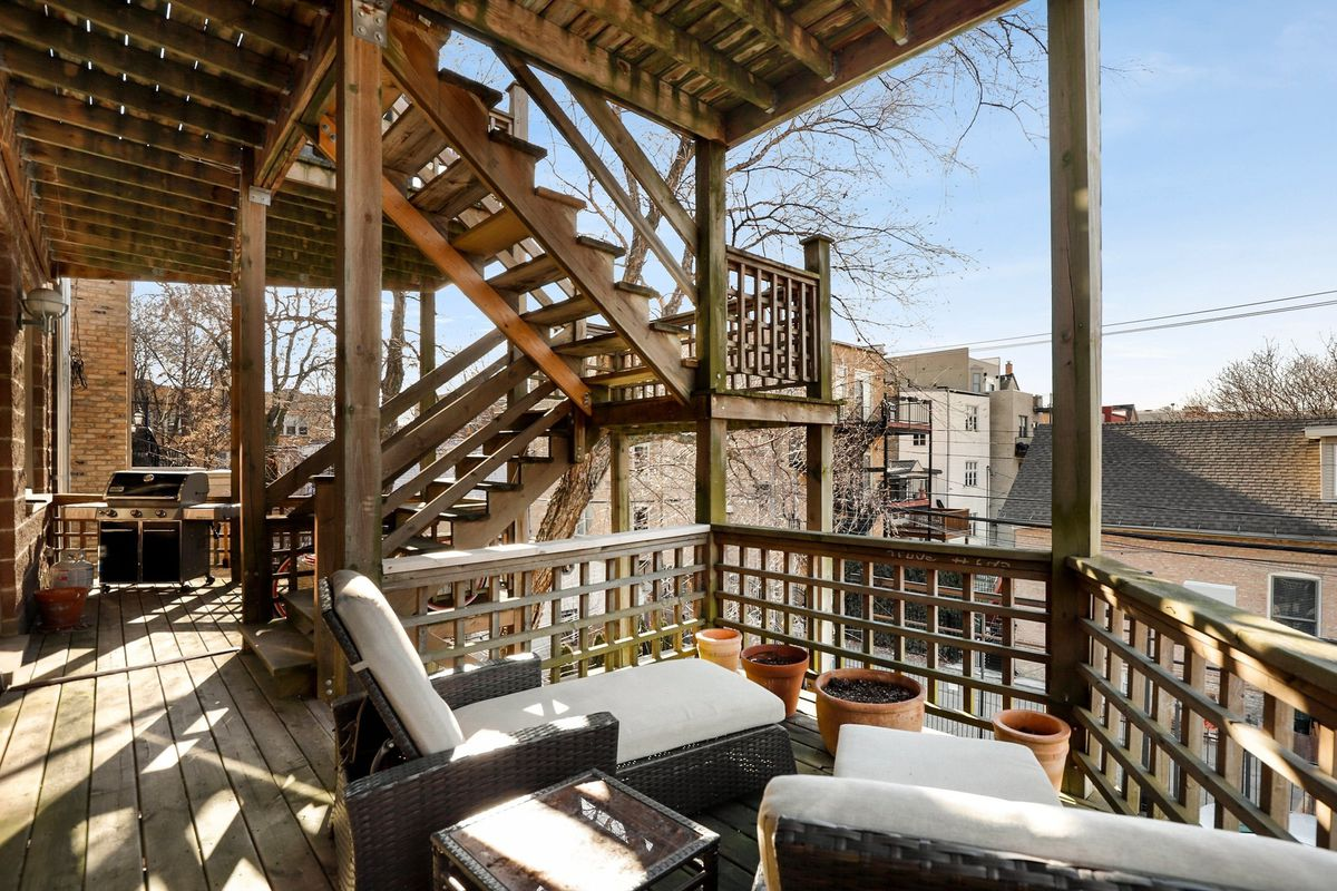 The back deck overlooks other homes in the neighborhood. There is a wooden railing and stairs. There are two lounge chairs with terracotta pots.