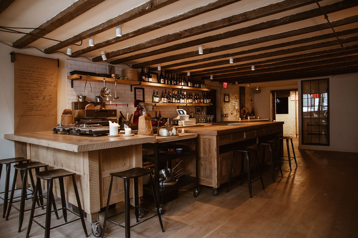 A bar with low-hanging ceilings, the whole space is covered in wood, both floors and ceiling, and there are stools around the wooden bar