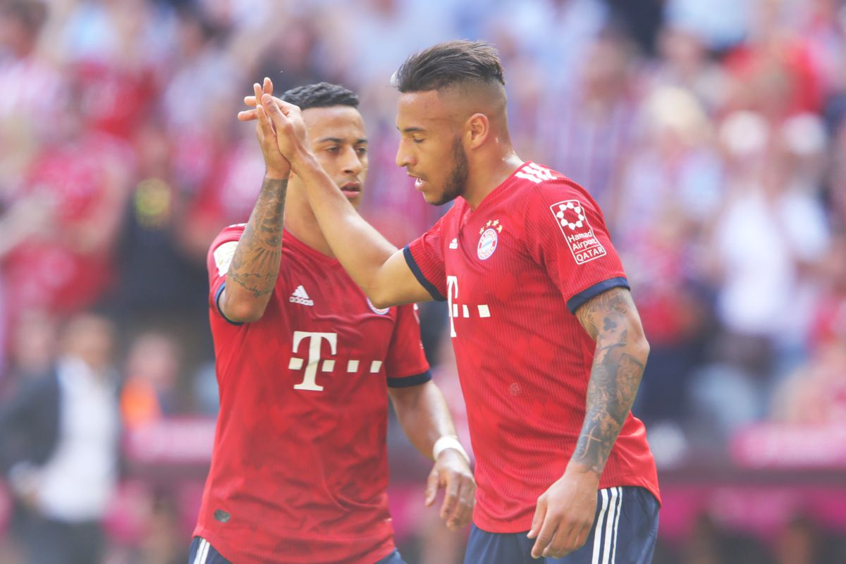 MUNICH, GERMANY - MAY 12: Corentin Tolisso of Bayern Muenchen celebrates with teammate Thiago Alcantara after scoring his sides first goal during the Bundesliga match between FC Bayern Muenchen and VfB Stuttgart at Allianz Arena on May 12, 2018 in Munich, Germany.