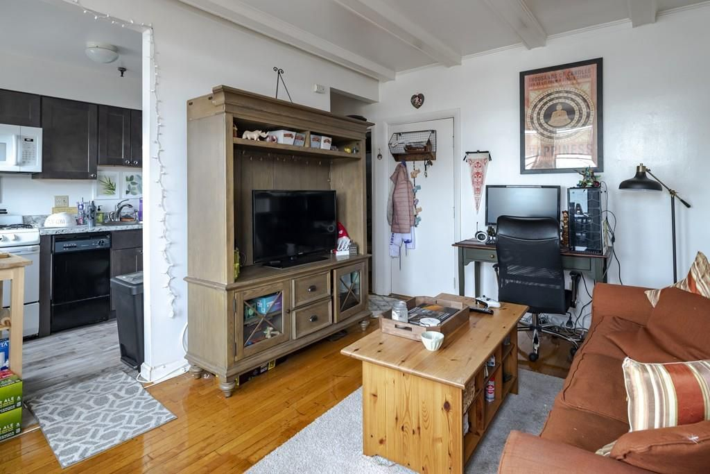 A view of the living room from the other end, with a TV stand and a coffee table figuring prominently.