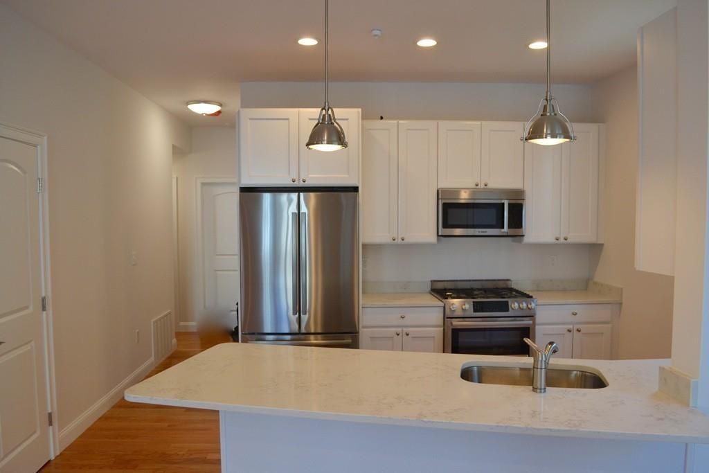 A modern kitchen as viewed over the granite countertop.