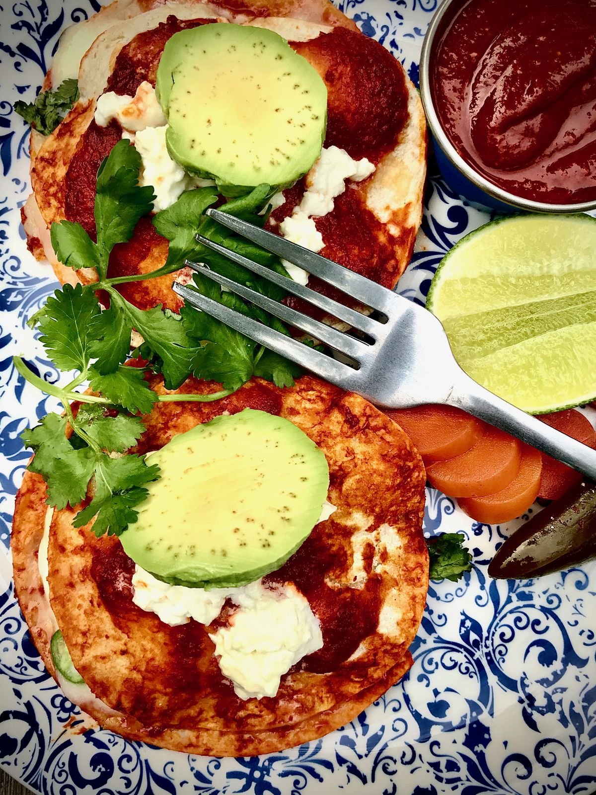 A metal forn sits next to memelas, fried masa cakes topped with salsa, beans, and Oaxacan cheese and slice of avocado and sprigs of cilantro