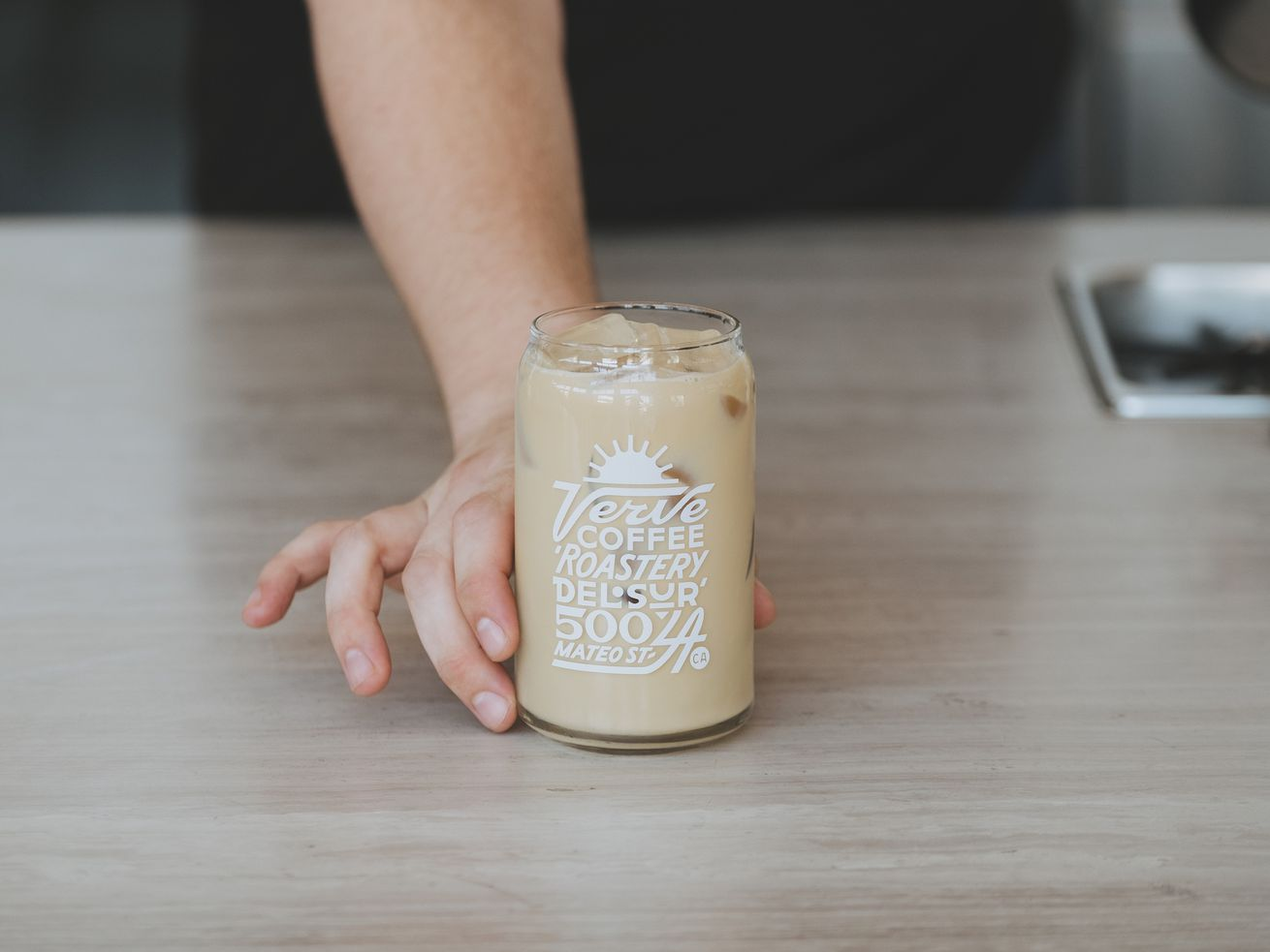 A latte in a tall glass, being slid across a table.