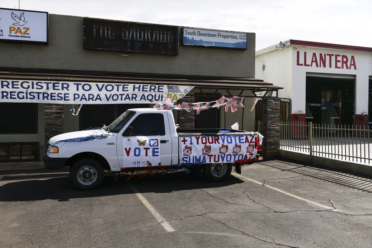 "A small pickup truck decorated with a garland of American flags carries signs that read ""Vote"" and ""+1 your vote AZ, suma tu voto AZ."""