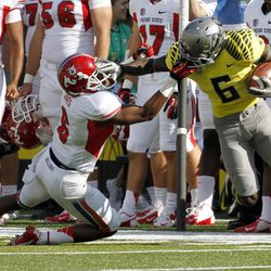 Oregon running back DeAnthony Thomas, right, is pulled down by his face mask by Fresno State defender L.J. Jones during the first half of an NCAA college football game in Eugene, Ore., Saturday, Sept. 8, 2012. Jones was called for a face-mask penalty on the play.