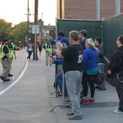 David Ross being escorted by security, as autograph seekers are held behind a barricade fence on Waveland