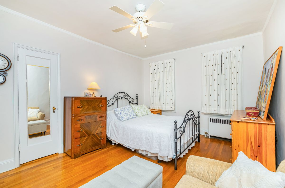 A bedroom with a small bed, white walls, a ceiling fan, and hardwood floors.